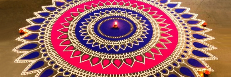 a purple and pink rangoli with lamps
